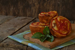 Salty snack. Homemade muffins with cheese, tomatoes and basil on wooden background. Savory pastry. Royalty Free Stock Photography