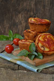 Salty snack. Homemade muffins with cheese, tomatoes and basil on wooden background. Savory pastry. Stock Photos