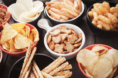Salty snacks. Salty crackers, tortilla chips and other savoury snacks with salsa dip Stock Photo
