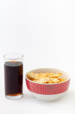 Salty snacks and juice in a glass on a white background Royalty Free Stock Photo