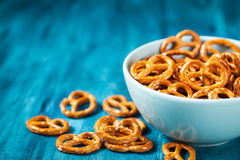 Salty snacks mini pretzels in bowl. On blue wooden table Stock Image
