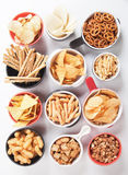 Salty snacks. Potato chips,pretzels, roasted peanuts and other salty snacks over white background Stock Photo