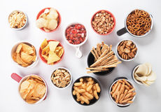 Salty snacks. Potato chips,pretzels, roasted peanuts and other salty snacks over white background Stock Image
