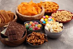 Salty snacks. Pretzels, chips, crackers in wooden bowls. Unhealthy products. food bad for figure, skin, heart and teeth. Assortment of fast carbohydrates food Stock Image