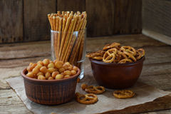 Salty snacks on wooden background. Crackers, pretzel, salted straws, nuts, dried fish. Junk food for beer or cola. Photographed wi Royalty Free Stock Images