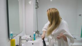Salud del pelo, concepto de la pérdida de pelo Mujer que se peina el cabello seco dañado rubio en el cuarto de baño metrajes