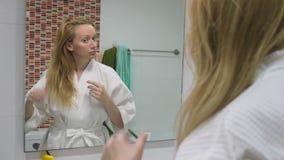 Salud del pelo, concepto de la pérdida de pelo Mujer que se peina el cabello seco dañado rubio en el cuarto de baño almacen de video