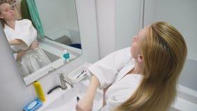 Salud del pelo, concepto de la pérdida de pelo Mujer que se peina el cabello seco dañado rubio en el cuarto de baño almacen de metraje de vídeo