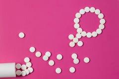 Salud femenina del concepto Símbolo del género hecho de píldoras o de tabletas rosadas en fondo rosado imagen de archivo