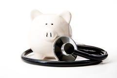 Salud financiera - estetoscopio y hucha negros fotografía de archivo libre de regalías