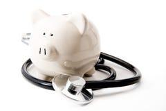Salud financiera - estetoscopio y hucha negros Imagen de archivo libre de regalías
