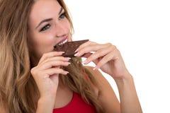 Salud, gente, comida y concepto de la belleza - adolescente sonriente precioso que come el chocolate Fotos de archivo libres de regalías