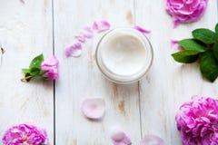 Salud natural y relajación poner crema cosméticas del producto del skincare rodeadas por el flor color de rosa en la tabla de mad fotografía de archivo libre de regalías