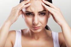 Salud y dolor Una mujer joven cansada, agotada que sufre de un dolor de cabeza severo de la tensión Retrato de una muchacha enfer foto de archivo libre de regalías