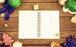 Saludando, cuaderno del papel en blanco con la decoración de la Navidad en la madera Fotografía de archivo