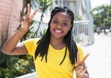 Saludando a la mujer africana en una camisa amarilla al aire libre en la ciudad Fotos de archivo libres de regalías