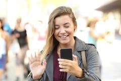 Saludo adolescente durante una llamada video Imagen de archivo