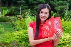 Saludo chino del Año Nuevo con Cheongsam y los peckets rojos Fotos de archivo libres de regalías