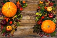 Saludo de la acción de gracias con las hojas y la calabaza en la tabla de madera Foto de archivo libre de regalías