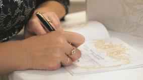 Saludo de la escritura de la mujer en el libro de saludos almacen de video