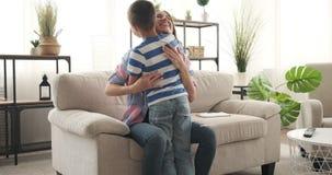 Saludo de la madre y del abarcamiento en su llegada hijo en casa almacen de metraje de vídeo