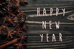 Saludo de la muestra del texto de la Feliz Año Nuevo con los conos del anís y del pino en w Foto de archivo libre de regalías