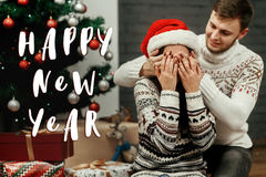 Saludo de la muestra del texto de la Feliz Año Nuevo con los pares felices de la familia, mano Fotografía de archivo libre de regalías