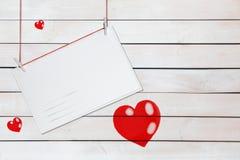 Saludo de la tarjeta de papel y de tres corazones rojos en fondo blanco de madera con el espacio de la copia imagen de archivo