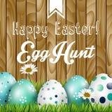 Saludo de Pascua, flores y huevos coloreados en la hierba en el fondo de madera
