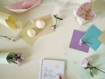 Saludo del día de madre, papel, materiales del arte, flores frescas en un fondo ligero imagen de archivo