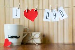 Saludo del d?a de padre Mensaje con el corazón de papel que cuelga con las pinzas sobre el tablero de madera Feliz cumplea?os fotos de archivo