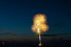 Saludo del fuego artificial de oro colorido sobre el mar Imagen de archivo