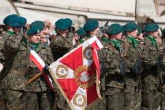 Saludo del soldado con el escudo de armas polaco Fotografía de archivo