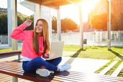 Saludo femenino feliz del adolescente hola mientras que se sienta con el ordenador portátil abierto al aire libre Imagen de archivo