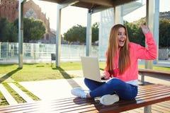 Saludo femenino feliz del adolescente hola mientras que se sienta con el ordenador portátil abierto al aire libre Fotos de archivo libres de regalías
