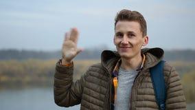 Saludo hermoso del hombre agitando su mano, al aire libre, retrato del primer del individuo en naturaleza de la mañana almacen de metraje de vídeo