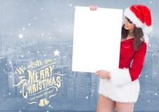 Saludos de la Feliz Navidad con la mujer que lleva a cabo el cartel en blanco Fotos de archivo