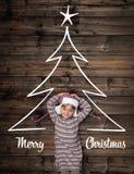 Saludos de la Feliz Navidad en madera oscura vertical del vintage de la visión superior Muchacha feliz del niño en pino del homew imagenes de archivo
