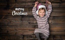 Saludos de la Feliz Navidad y de la Feliz Año Nuevo en madera oscura vertical del vintage de la visión superior Muchacha feliz he fotos de archivo libres de regalías