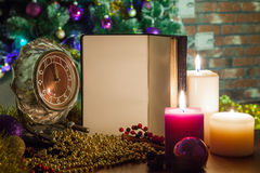 Saludos de la Navidad en un cuaderno abierto con un reloj y una vela en decoraciones de la Navidad Imagenes de archivo