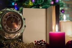 Saludos de la Navidad en un cuaderno abierto con un reloj y una vela en decoraciones de la Navidad Foto de archivo libre de regalías