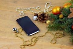 Saludos del teléfono Smartphone y árbol de navidad en backgrou de madera Foto de archivo