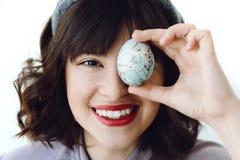 Saludos felices de Pascua Mujer joven hermosa en oídos del conejito que sonríe y que sostiene el huevo de Pascua cerca de cara en fotos de archivo