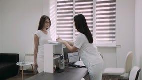 Saluez pour consulter le patient féminin sur la réception de clinique 4K clips vidéos