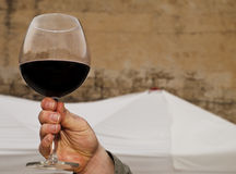 Salut. Male hand holding up a glass of cabernet red wine Stock Photography