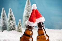 Salut! Two beer bottles saying cheers. Fresh draught lager beer cooled well on winter background royalty free stock photography
