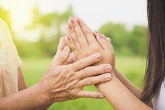Salutation asiatique de fille ou payer le respect à sa mère, deux mains tenant chacun d'autres image stock