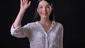 Salutation attrayante de jeune femme et invitation de quelqu'un, se tenant d'isolement sur le fond noir clips vidéos
