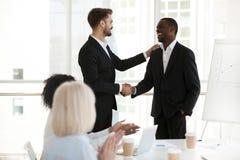 Salutation caucasienne des employés de noir de poignée de main de patron avec le succès image stock