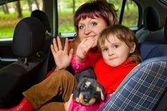 Salutation de femme et de fille pour onduler des mains dans le véhicule Photo libre de droits